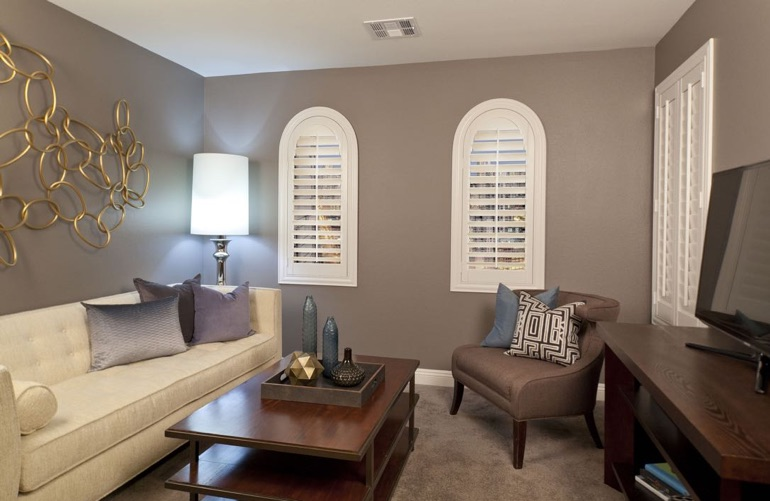 Family room with plantation shutters on arched windows and rectangular window