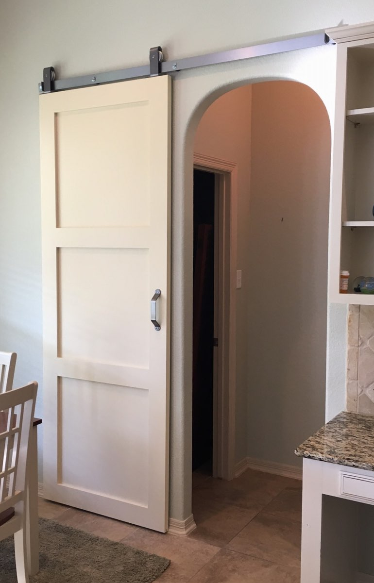 White sliding barn door covering bedroom doorway
