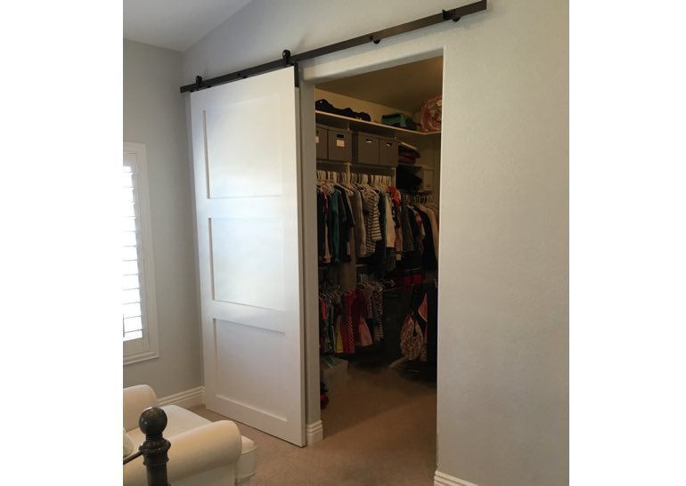 White sliding barn door covering closet