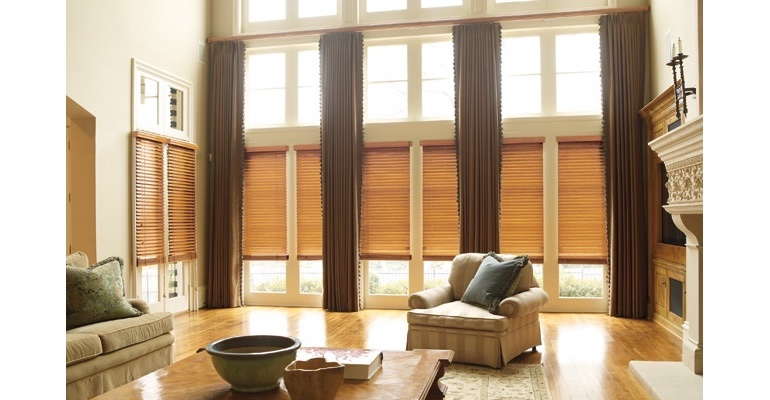 Destin great room with natural wood blinds and floor to ceiling draperies.
