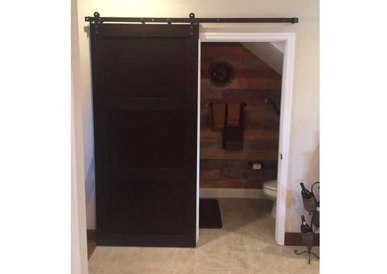 Brown sliding barn door covering bathroom entry