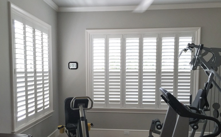 Destin fitness room with shuttered windows.