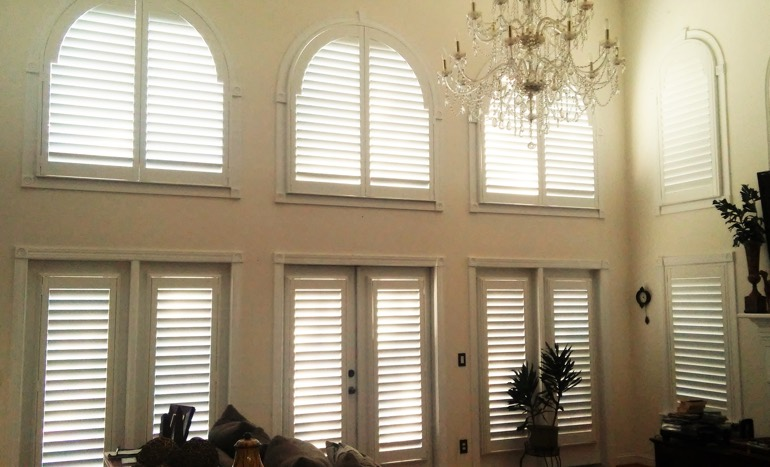Television room in two-story Destin house with plantation shutters on tall windows.