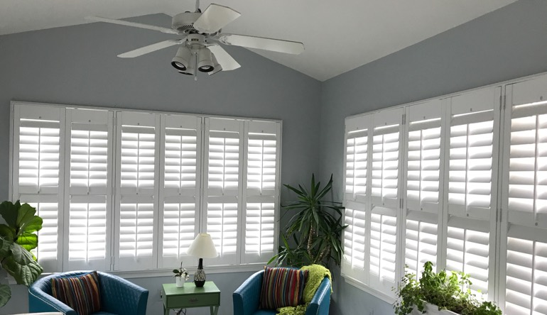 Destin living room with fan and shutters