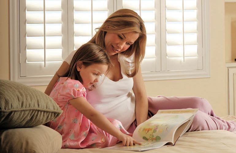 Mother and girl reading on bed with shuttered windows.