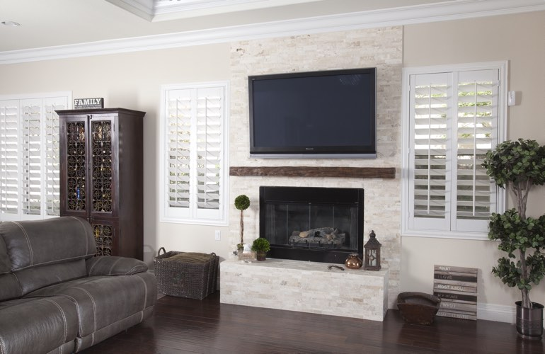 White plantation shutters in a Destin living room with dark hardwood floors.
