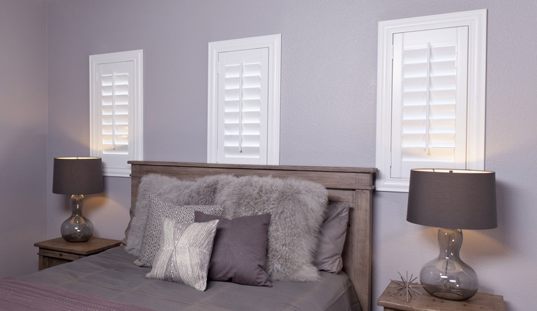 White plantation shutters in Destin bedroom windows.