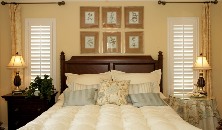 Bedroom with two tall plantation shutters on either side of bed in Destin