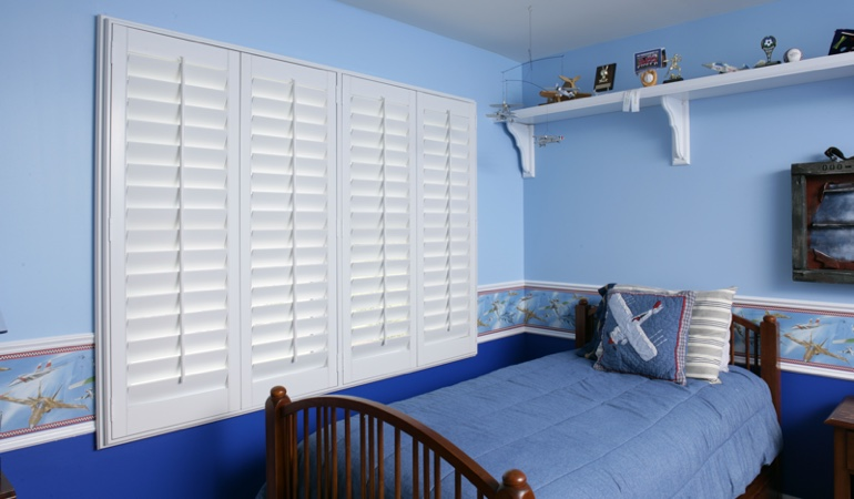 Blue kids bedroom with white plantation shutters in Destin